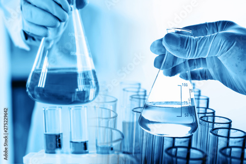 Fotografia hand of scientist holding flask with lab glassware and test tubes in chemical la