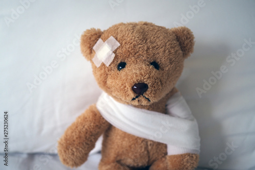 Fotografie, Obraz  Sad bear doll lying sick in bed with the wound on the head and bandage