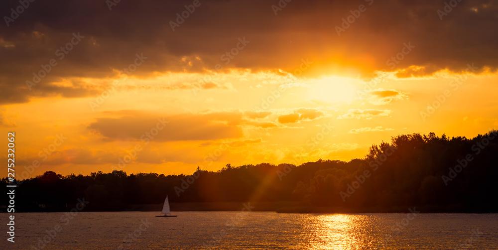 Orange romantic sunset over lake on a beautiful summer evening.