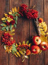 Autumn Wrench Decor. Colorful Fall Plants, Leaves Arranged In Round Frame On Brown Wooden Background. Copy Space.
