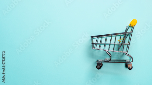 Shopping cart on blue background. Top view or flat lay. Shop trolley at supermarket as sale, discount, shopaholism concept with copy space for text or design. Consumer society trend.