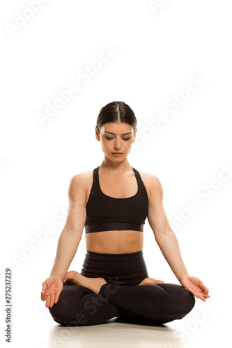 Young woman siting in lotus yoga position meditating on white background