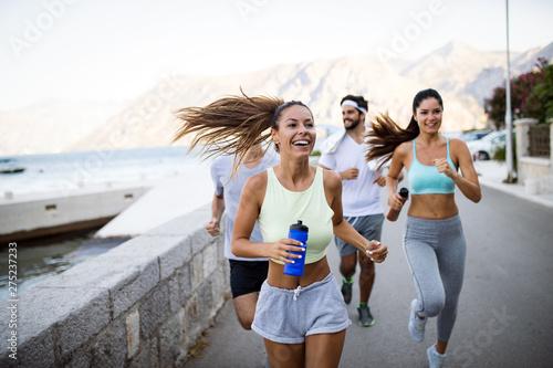Foto op Canvas Op straat Outdoor portrait of group of friends running and jogging in nature