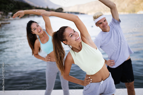 Foto op Canvas Op straat Fit group of happy people exercising outdoor. Smiling friends doing fitness workout