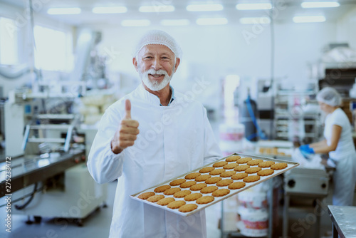 Fotografie, Obraz  Portrait of senior adult food plant worker in sterile white uniform holding tray with cookies and giving thumbs up