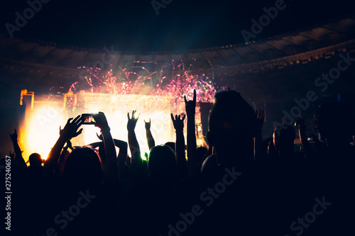 Silhouette of a concert crowd. The audience applauds the musicians on stage. The bright spotlight and dancing people. - 275240657