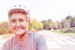 Leinwanddruck Bild - Smiling senior woman wearing cycling helmet in park