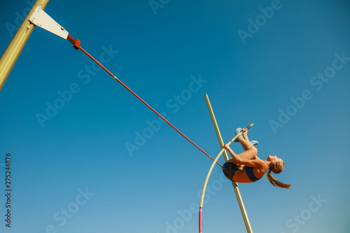 Obraz na plátně Professional female pole vaulter training at the stadium in sunny day