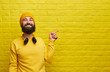 Cheerful hipster pointing at yellow wall