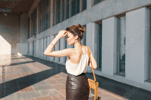 Refined young woman in leather skirt and silk blouse thinking how to solve a situation Fototapeta