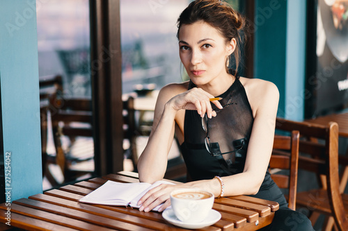 Fotografia  Elegant young woman took off her glasses while taking a break of her agenda