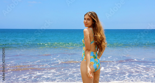 In de dag Bleke violet Beautiful young latin woman in swimsuit turn and looks to the camera on tropical beach. Portrait of happy young woman smiling at sea. Brunette tanned girl in swimwear enjoying and walking on beach.