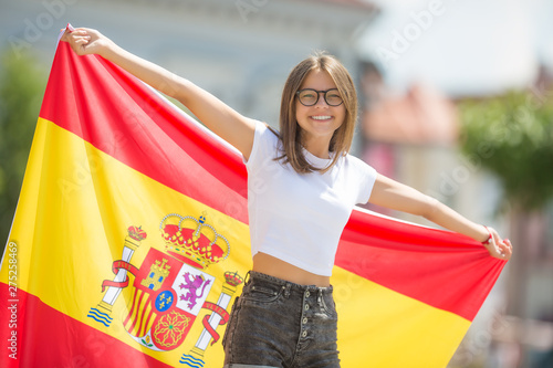 Happy girl tourist walking in the street with spanish flag Canvas