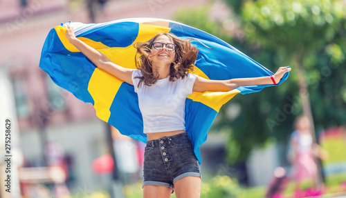 Fotomural  Happy girl tourist walking in the street with sweden flag