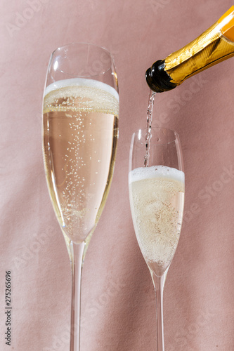 Prosecco flutes and a bottle, an italian sparkling wine on pink romantic background