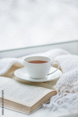 Photo sur Toile The Warm knitted scarf, a cup of hot tea and a book