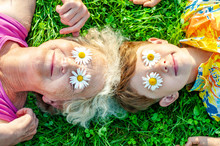 Happy Family - Grandmother With Grandson Having Fun Lying On The Lawn With Daisies On Their Eyes. Summer Vacation With My Grandmother. Family Relationships And Friendship
