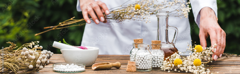 Fototapety, obrazy: panoramic shot of woman holding gypsophila flowers near bottles with pills