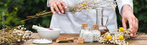 Photo  panoramic shot of woman holding gypsophila flowers near bottles with pills