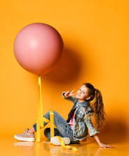 Young Beautiful Teenager Girl Posing On A Yellow Background, Lies And Holds Up A Huge Giant Pink Balloon. Summer Style.