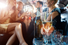 Women And Men Celebrating With Drinks In A Limousine Car