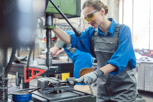 Fotomural  Metal worker woman operating drilling machine