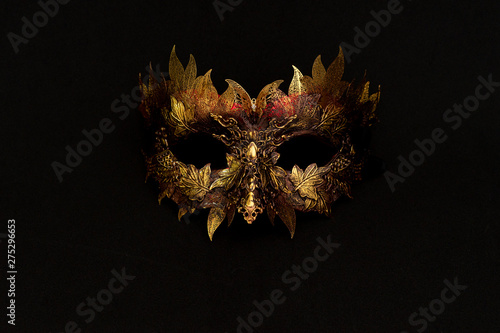Venetian mask in gold and red with metallic pieces in the form of leaves Canvas Print