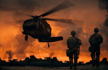 Military Soldiers Walking To Helicopter In Battlefield At Sunset