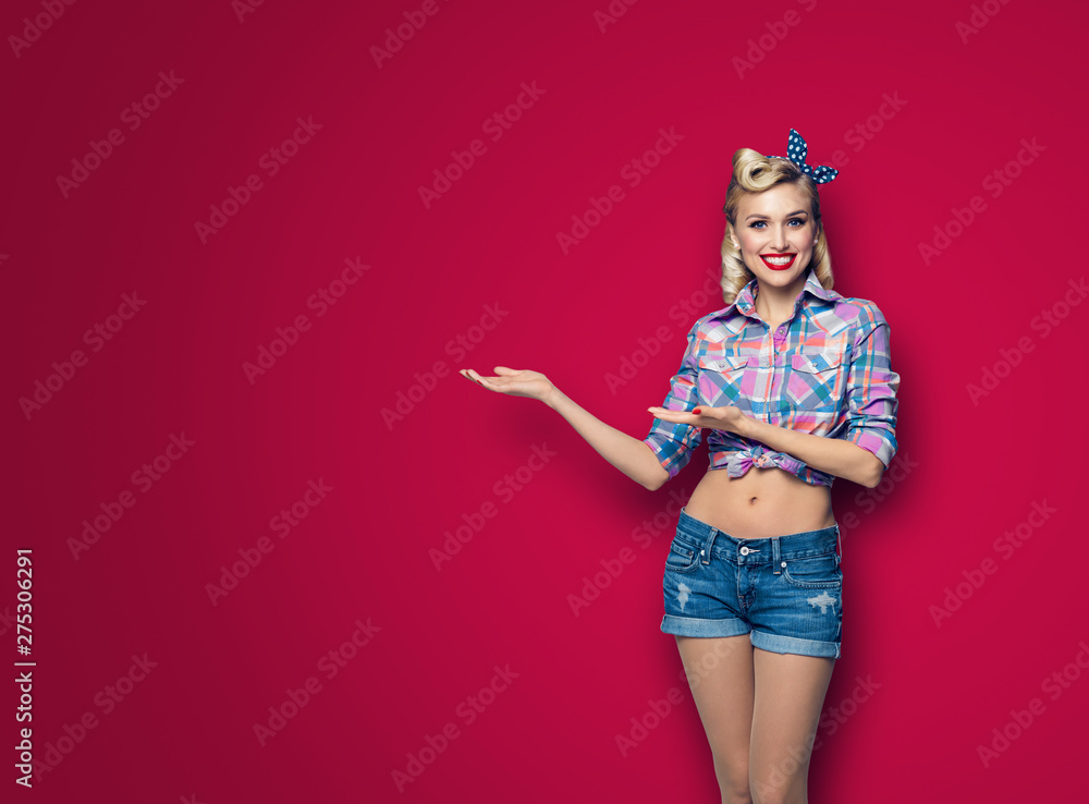 Fototapety, obrazy: Photo of woman in pin up style, showing something or copyspace, over dark red background