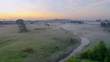 Beautiful underground fog over a small river among grassy meadows in rural areas, early in the morning at dawn