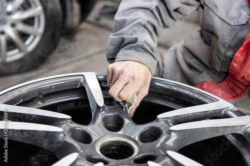 Foto Master body repair man is working on preparing the surface of the aluminum wheel