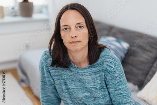 Fotografía  ernste Frau sitzt auf dem sofa und schaut in die kamera