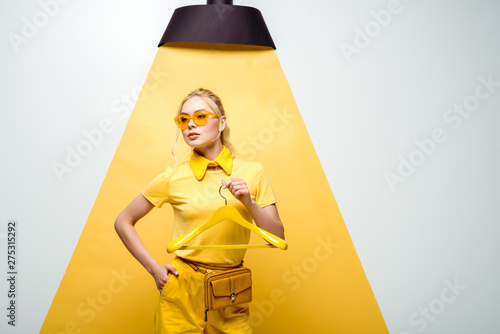 Obraz attractive woman in sunglasses holding hanger and standing with hand in pocket on white and yellow - fototapety do salonu