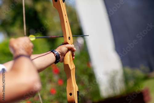 Canvas Print Archer holding wooden bow and getting ready to aim at the target