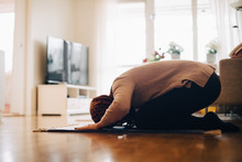 Full Length Of Woman Praying On Carpet At Home