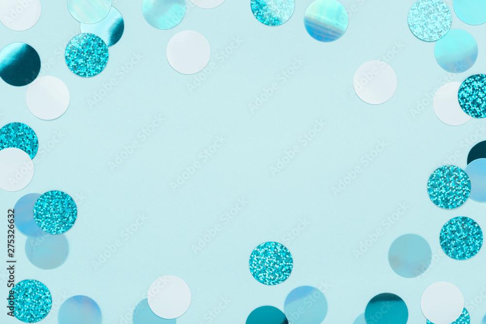 Fototapeta Festive frame of iridescent confetti sparkling on pastel blue background. Holiday backdrop. Flat lay, copy space. - obraz na płótnie