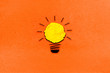 creative inspiration from yellow concept crumpled paper turn on light bulb metaphor for good idea concept on orange paper background / best solution think answer