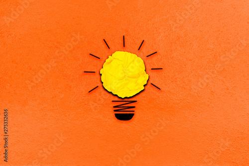 twórcza inspiracja z żółtego pojęcia zmięty papier włącz metaforę żarówki na dobry pomysł koncepcja na pomarańczowym tle papieru / najlepsze rozwiązanie pomyśl odpowiedź