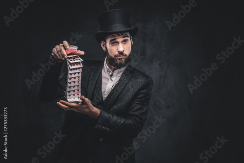 Cuadros en Lienzo A Bearded magician in a black suit and top hat, showing trick with playing cards on a dark background