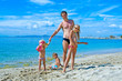 happy dad with three children on the sea in sunny weather