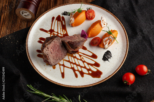 Photo  Roasted and sliced in halves filet mignon, served with mashed sweet potatoes and