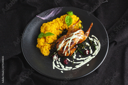 Photo  Whole quail roasted with a golden crust, served with yellow milanese risotto and
