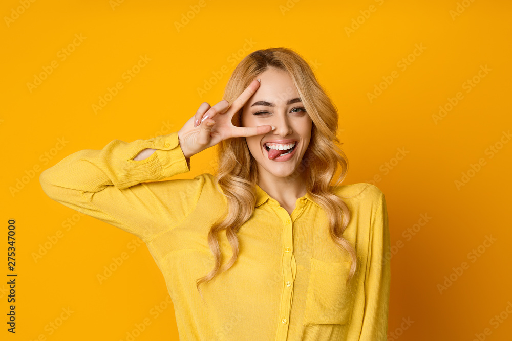Fototapety, obrazy: Pretty Girl Winking, Showing Tongue and Peace Gesture