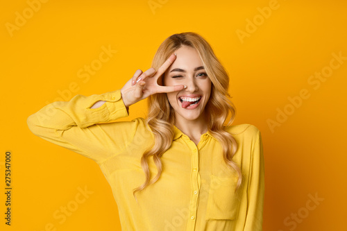 Photo  Pretty Girl Winking, Showing Tongue and Peace Gesture