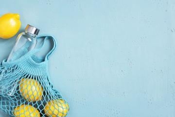 Blue background with mesh bag, glass bottle and fresh lemons
