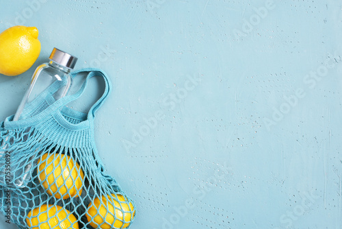 Blue background with mesh bag, glass bottle and fresh lemons
