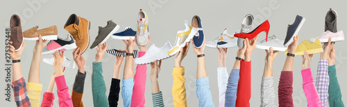 Vászonkép Set of people holding different stylish shoes on color background, closeup