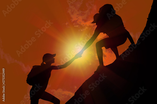 Fototapety, obrazy: Silhouette of man helping woman to climb on hill against sunset