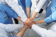 Team of medical workers holding hands together indoors, top view. Unity concept