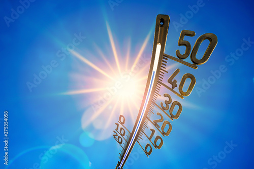 Poster Fleur Hot summer or heat wave background, bright sun on blue sky with thermometer